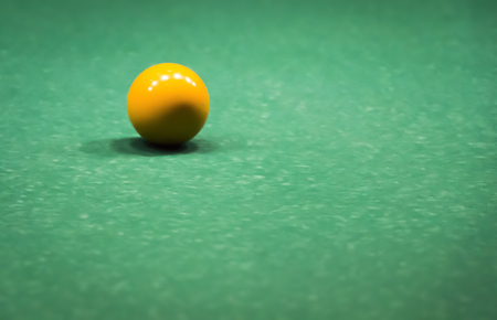 Colored ball on a green billiard table close-up.