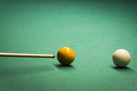 Colored balls on a green billiard table close-up.