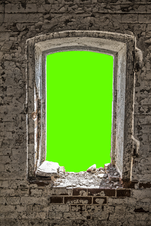 A view from a window hole of an old dilapidated abandoned house. Green background for image insertion.