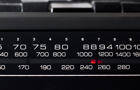 Black dial and red arrow of a portable radio close-up.