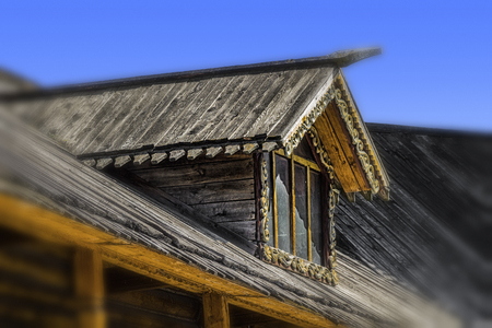 The upper attic window of the old wooden house.