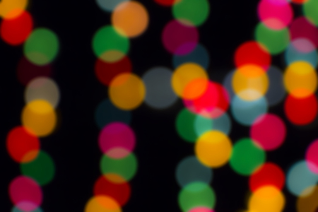 Blurred bokeh colorful lights lanterns, holiday new year lighting on black background Christmas winter glitter shiny light bokeh in rainbow colors.