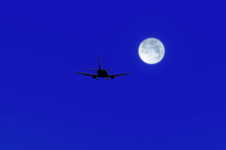 The black silhouette of a passenger airplane flying towards the moon.