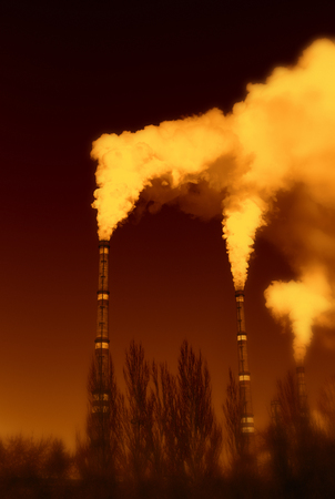 The thick smoke rises high from the industrial pipes. Pollution of the environment with waste products. Archivio Fotografico