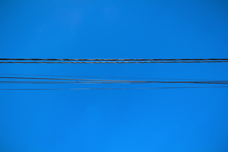 A line of electric wires close-up against a blue sky.
