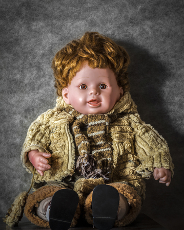 The boy's doll sits in a dark attic close-up.