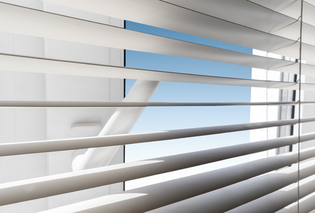 White plastic window with blinds close-up against a blue sky.