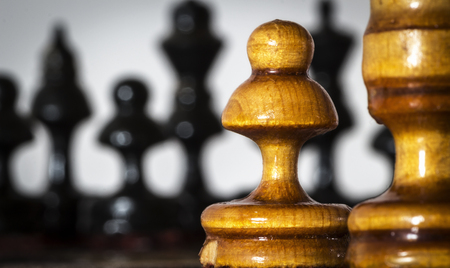 Wooden chess pieces stand on the board in the starting position before the battle. Stock Photo
