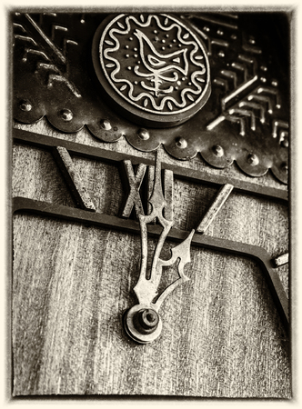 Old wooden cuckoo clock in old photo style closeup.
