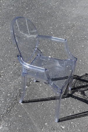 A chair of transparent plastic stands on the street.