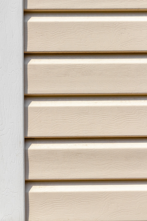 Coating of walls from beige siding close-up.