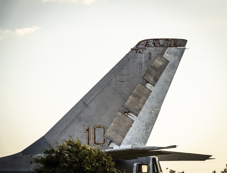 The tail of an old military aircraft standing in the park.
