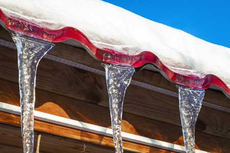 Transparent icicles from the roof glisten in the sun. Reklamní fotografie