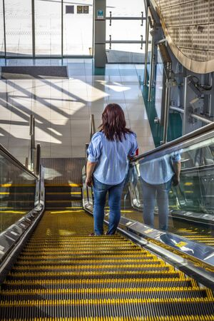 Woman on the escalator of a subway station..