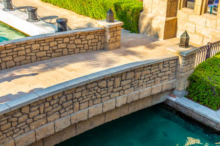 Decorative stone bridge through an artificial channel with azure water. 版權商用圖片