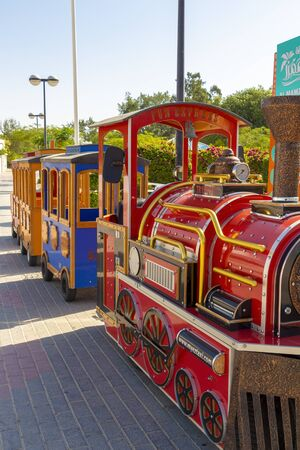 Children's colorful train awaits departure in the amusement park.
