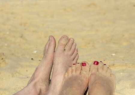 Legs of a woman and a man on a sandy beach.