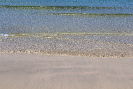 Clear sea water washes the sandy shore of the beach.