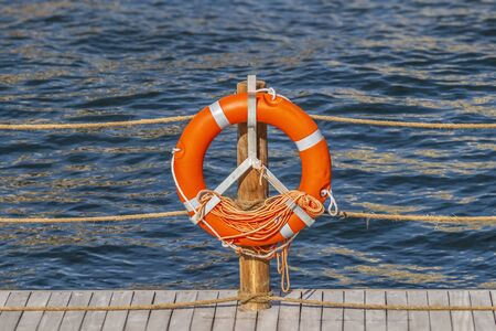 Lifebuoy on the pier on the background of the blue surface of the water.