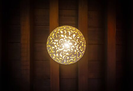 The lamp in the Arab style hangs on the ceiling of a dark room.