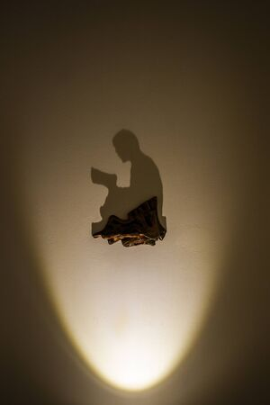 Shadow on the wall in the form of a praying Arab.