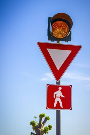 Traffic signs attract attention before a pedestrian crossing.