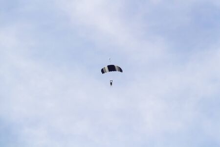 Paraglider flies high in the blue sky.