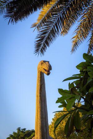 Dinosaur head on a long neck in an amusement park, a historical museum.