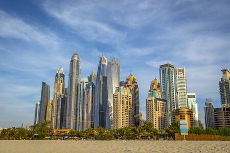View of the high-rise buildings of Dubai from the beach. Dubai Marina district. 2018. 写真素材