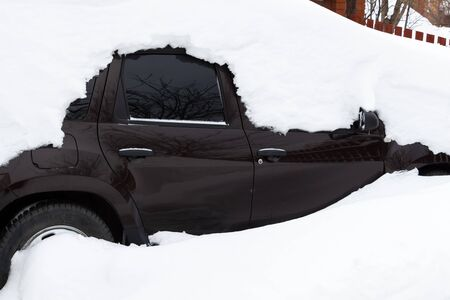 The car was completely covered with snow in the backyard.