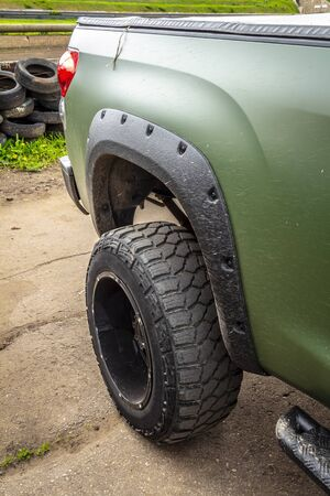 Wheel of green offroad pickup truck close-up.