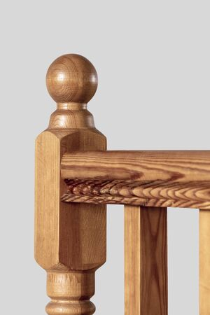 Element of a wooden interior staircase. Wooden baluster close-up.