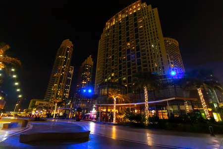 Dubai, UAE - November 28, 2018: District downtown. View of the beautiful modern high-rise buildings in evening time. Walk through the night streets of Dubai.