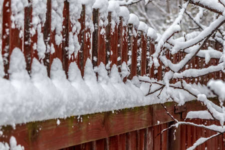 Rural wooden fence covered with freshly fallen snow. Zdjęcie Seryjne