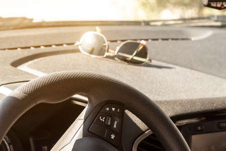 Sunglasses lie on the dashboard of a car while waiting for a ride.
