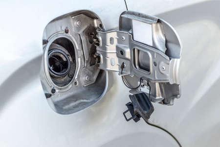 Open fuel filler neck of a passenger car close-up.