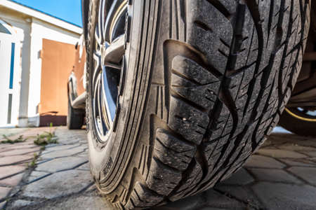 Tread of a wheel of an off-road car standing in the back yard, closeup. 免版税图像
