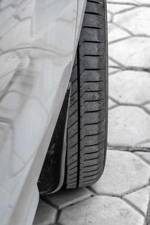 Tread of a wheel of car standing in the back yard, closeup. 免版税图像