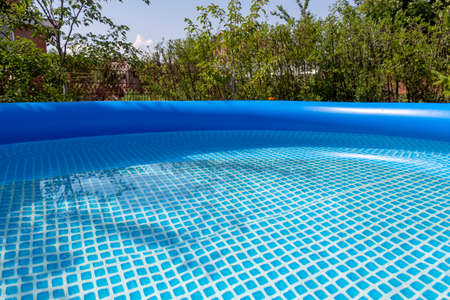 Part of a blue inflatable pool in the backyard of a private house.