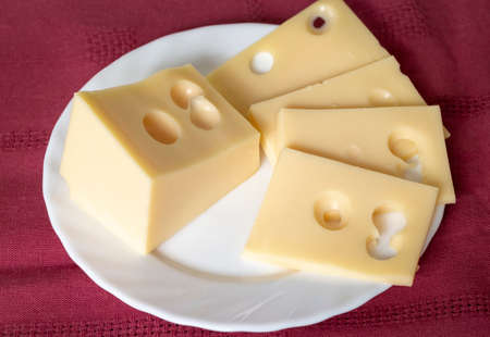 The cheese lies on a close-up of a white porcelain plate. 免版税图像