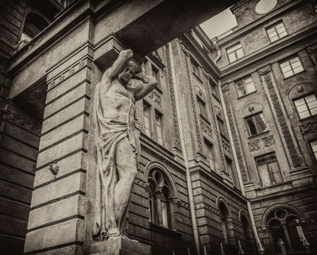 Fragment of historic stone building of St. Petersburg with a sculpture. Old photo style.