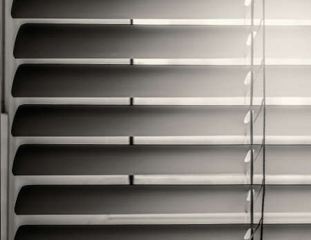Close-up of horizontal blinds in a half-open state. In sepia tones.