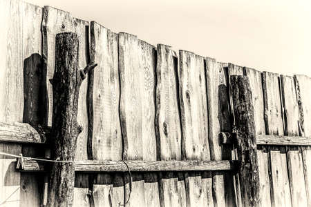 Part of old wooden rural fence on a background of blue sky. Black and white sepia.