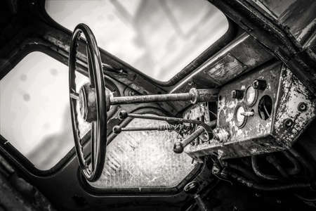 The instrument panel and steering wheel of the old rusty abandoned tractor. Black and white photo.