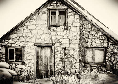 Old abandoned stone house on an old black and white photo.