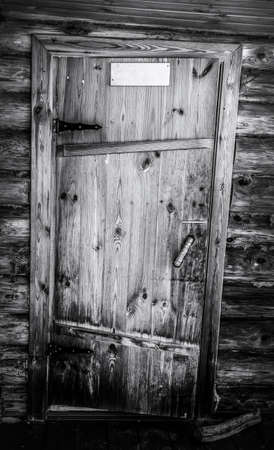 The old rickety door of a wooden log house. Black and white photo. Zdjęcie Seryjne