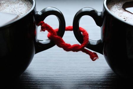 Dva šálky kávy související s červenou nití