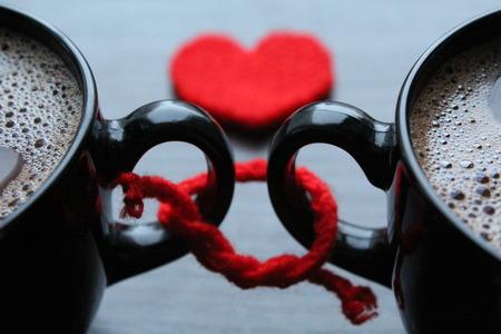 Dva šálky kávy a červené srdce na pozadí
