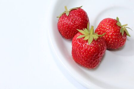 Red strawberries on a white dish