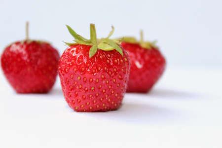 Červené jahody na bílém pozadí